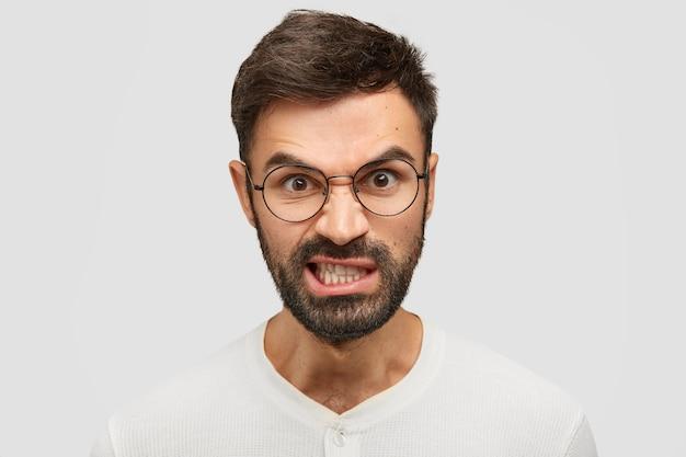 Zirytowany Młody Europejczyk Zaciska Zęby Z Irytacją, Ma Wściekły Wyraz, Unosi Brwi W Złości Darmowe Zdjęcia