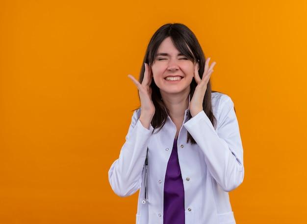 Zirytowany Młody Lekarz Kobiet W Szlafroku Ze Stetoskopem Zamyka Uszy Palcami Na Odosobnionym Pomarańczowym Tle Z Miejsca Na Kopię Darmowe Zdjęcia