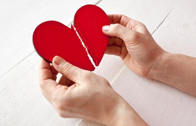 Złamane Czerwone Drewniane Serce W Rękach Kobiety Premium Zdjęcia