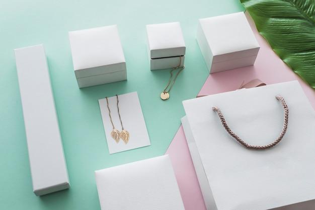 Złoci Biżuterii Pudełka Z Torba Na Zakupy Na Pastelowym Tle Premium Zdjęcia