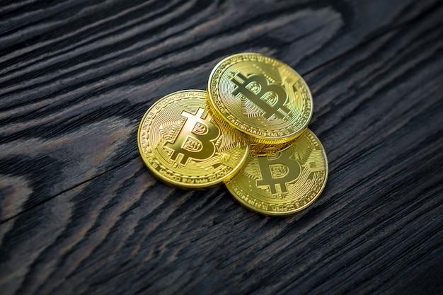 Złocisty Bitcoin Na Nowożytnym Telefonie Komórkowym Na Drewnianym Stole Premium Zdjęcia