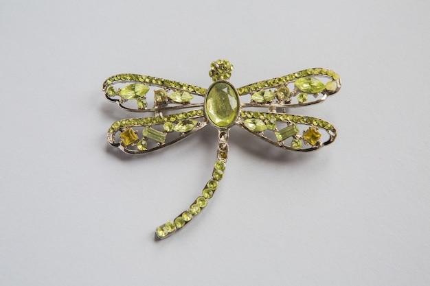Złota Broszka W Kształcie Z Zielonych Kamieni Na Białej Powierzchni Premium Zdjęcia