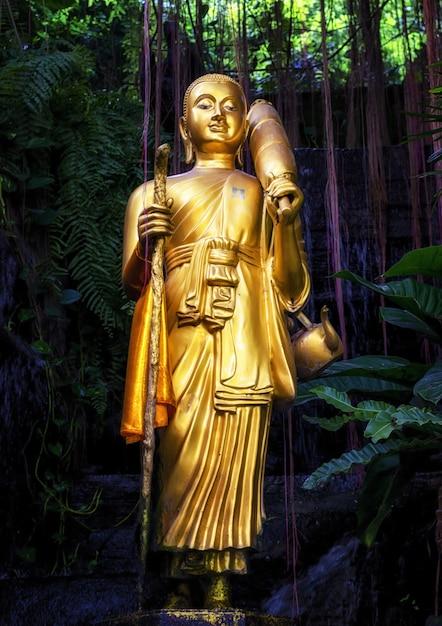 Złota buddha statua i mała sztuczna siklawa przy złotą górą przy watem saket w bangkok, tajlandia. Premium Zdjęcia