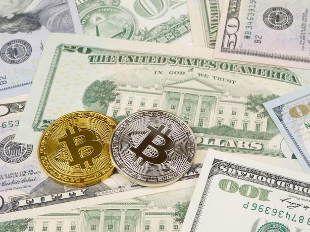 Złota i srebrna moneta bitcoin na nas dolarów z bliska. Premium Zdjęcia