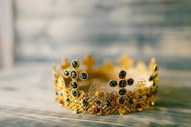 Złota Korona Wysadzana Drogocennymi Kamieniami Na ślub W Kościele Na Drewnianym Stole Premium Zdjęcia