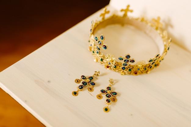 Złota Korona Z ślubnymi Krzyżami I Złote Kolczyki Wysadzane Drogocennymi Kamieniami Premium Zdjęcia