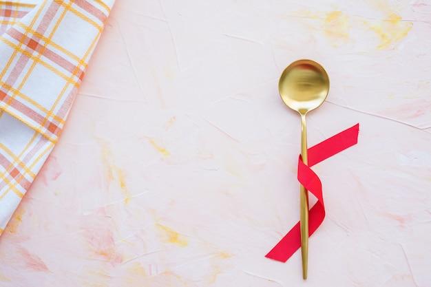 Złota łyżka W Czerwonej Wstążce I Ręcznik Kuchenny Na Różowym Tle Premium Zdjęcia