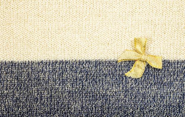 Złota wstążka na tle dwóch tonów tkaniny tekstury Premium Zdjęcia