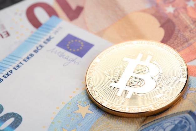 Złote bitcoiny ułożone na tle banknotów euro. Premium Zdjęcia