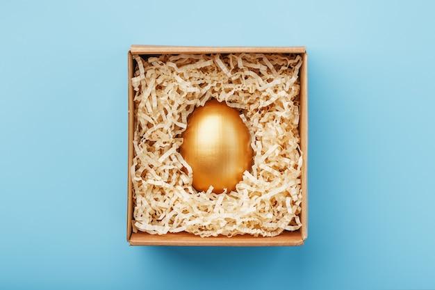 Złote Jajko W Pudełku Na Niebieskim Tle Koncepcja Wyłączności, Najlepszy Wybór, Nagroda, Specjalna Niespodzianka, Drogi Prezent. Premium Zdjęcia