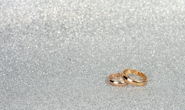 Złote Obrączki Dla Nowożeńców Na Srebrnym Tle Z Bokeh Zbliżenie Premium Zdjęcia