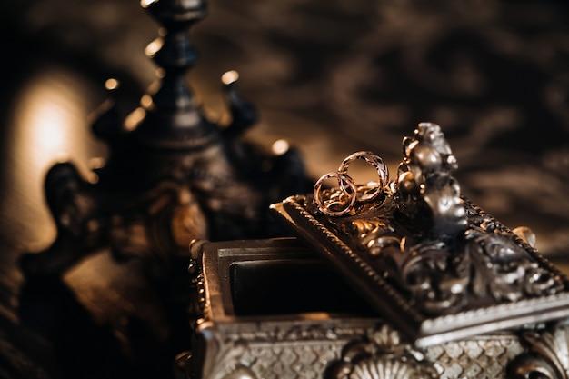 Złote Obrączki ślubne Leżą Na Antycznym Pudełku Z Biżuterią. Obrączki ślubne Na Uroczystości. Premium Zdjęcia