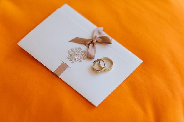 Złote obrączki ślubne leżą na białej karcie zaproszenie na pomarańczowym tle Premium Zdjęcia