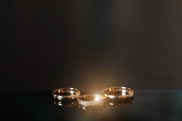 Złote Obrączki ślubne Leżą Na Drewnianym Stole Premium Zdjęcia