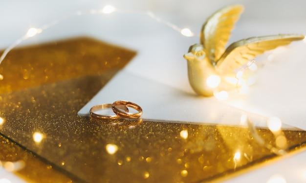 Złote Obrączki ślubne Na Złotym Tle Z Zabawkowym Ptakiem I Dekoracjami. Premium Zdjęcia