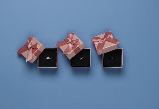 Złote Pierścienie W Pudełkach Na Prezent Na Niebieskim Tle. Sklep Jubilerski. Widok Z Góry Premium Zdjęcia
