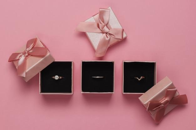 Złote Pierścienie W Pudełkach Na Różowym Pastelowym Tle. Sklep Jubilerski. Widok Z Góry Premium Zdjęcia