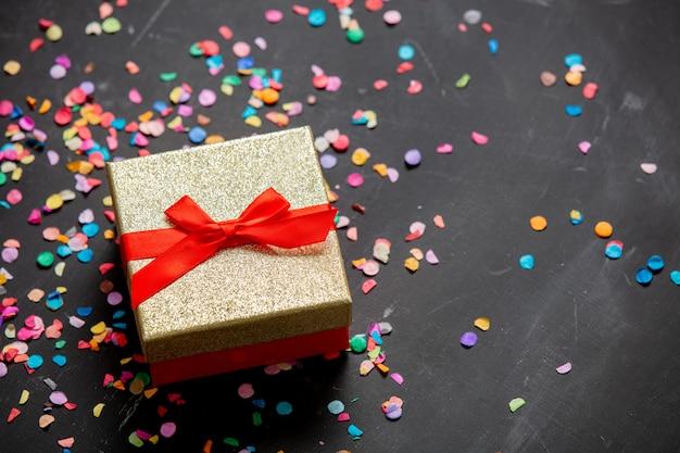 Złote Pudełko Z Czerwoną Wstążką I Konfetti Wokół Premium Zdjęcia