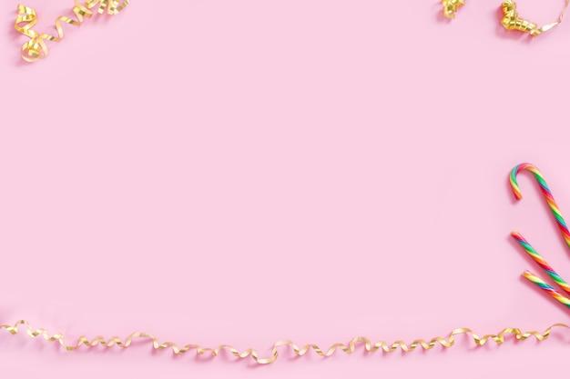 Złote serpentyny serpentyn i cukierki laski na pastelowym różowym tle Premium Zdjęcia
