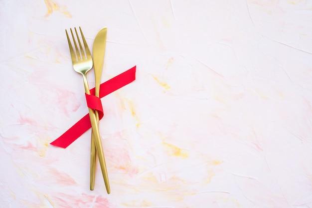 Złote Sztućce W Czerwoną Wstążką Na Różowym Tle Premium Zdjęcia