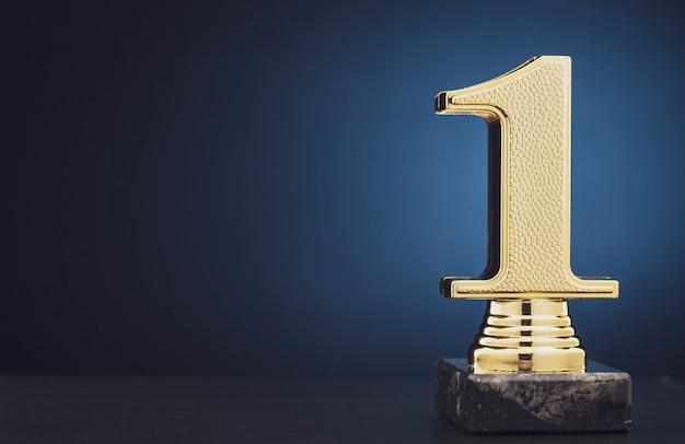 Złote trofeum mistrza lub zwycięzcy nad niebieskim Premium Zdjęcia