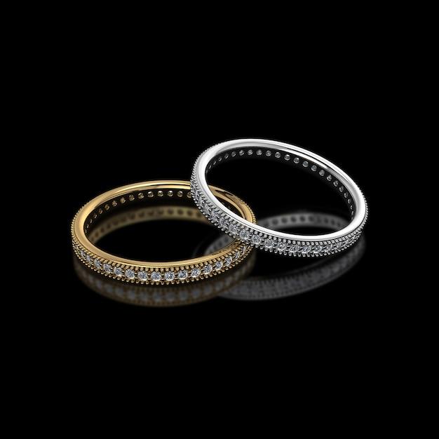Złoto i srebro z diamentowymi obrączkami ślubnymi na czarnym tle Premium Zdjęcia