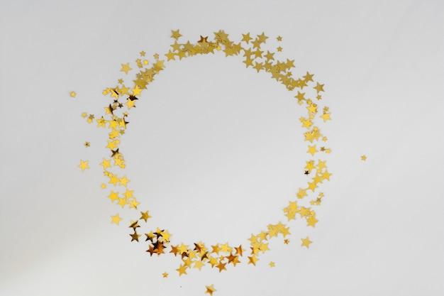 Złoty brokat rama koło, gwiazdy konfetti na białym tle. boże narodzenie, przyjęcie lub urodziny tło. Premium Zdjęcia