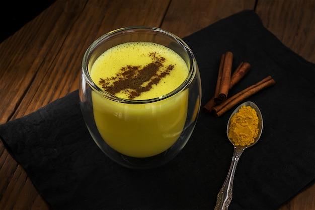 Złoty Latte Z Cynamonem. Tradycyjne Indyjskie Mleko Z Kurkumy Premium Zdjęcia