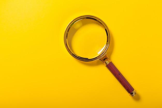 Złoty Lupa Na żółtym Tle Papieru Premium Zdjęcia