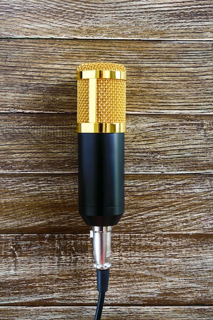 Złoty Mikrofon Pojemnościowy Leży Na Drewnianym Stole Z Miejscem Na Kopię. Motyw Muzyczny. Leżał Na Płasko. Widok Z Góry. Premium Zdjęcia