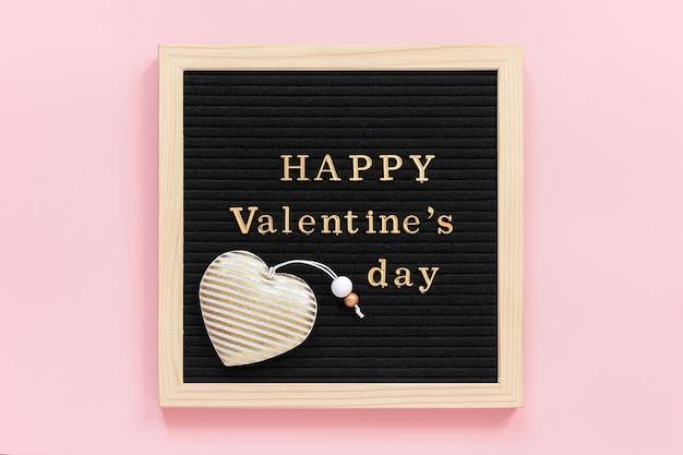 Złoty Napis Happy Valentines Day I Ozdoba Tekstylne Serce Na Czarnej Tablicy, Centralny Skład Na Różowym Tle. Premium Zdjęcia
