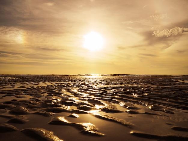 Złoty piasek wsady powierzchni wzór na zachód słońca plaża. Premium Zdjęcia
