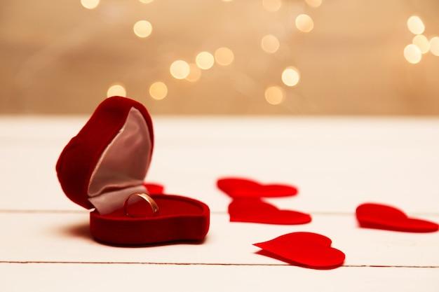 Złoty Pierścionek, Obrączka W Czerwonym Pudełku I Czerwone Serce Na Biało-czerwonym Tle Z Pięknym Bokeh Premium Zdjęcia