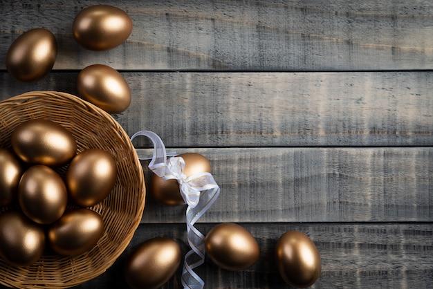 Złoty Wielkanocni Jajka W Gniazdeczku I Piórko Na Drewnianym Tle. Premium Zdjęcia