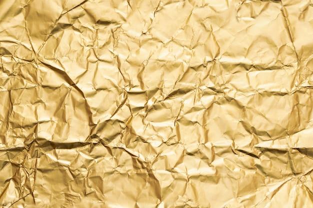 Złoty zmięty folia papieru tekstury abstrakta tło Premium Zdjęcia