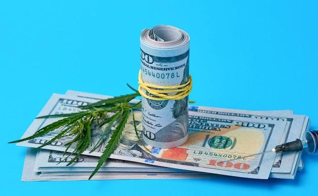 Złożona gotówka w dolarach amerykańskich, zielony liść konopi Premium Zdjęcia
