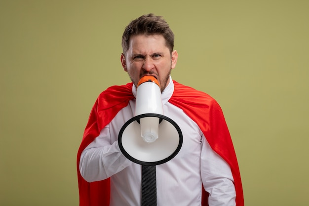 Zły Biznesmen Super Bohater W Czerwonej Pelerynie Krzycząc Do Megafonu Z Agresywnym Wyrazem Stojącym Na Zielonym Tle Darmowe Zdjęcia
