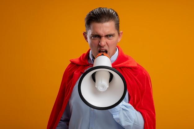 Zły Biznesmen Super Bohater W Czerwonej Pelerynie Krzyczy Do Megafonu Z Agresywnym Wyrazem Twarzy Stojącej Nad Pomarańczową ścianą Darmowe Zdjęcia