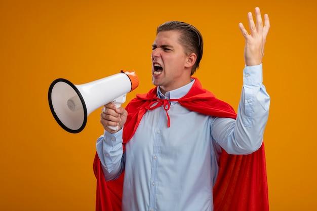 Zły Biznesmen Super Bohater W Czerwonej Pelerynie Krzyczy Do Megafonu Z Agresywnym Wyrazem Z Podniesioną Ręką Stojącą Na Pomarańczowym Tle Darmowe Zdjęcia