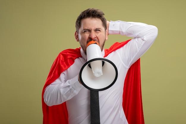 Zły Biznesmen Super Bohater W Czerwonej Pelerynie Krzyczy Do Megafonu Z Agresywnym Wyrazem Z Podniesioną Ręką Stojącą Na Zielonym Tle Darmowe Zdjęcia