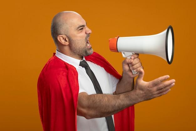 Zły Biznesmen Super Bohater W Czerwonej Pelerynie Krzyczy Do Megafonu Z Wyciągniętą Ręką Stojącą Nad Pomarańczową ścianą Darmowe Zdjęcia
