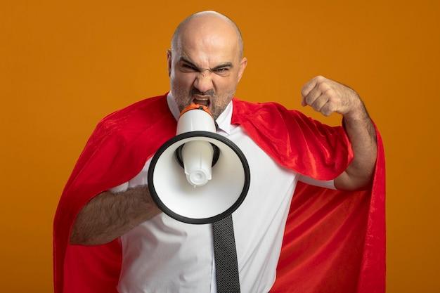 Zły Biznesmen Super Bohater W Czerwonej Pelerynie Krzyczy Do Megafonu, Zaciskając Pięść Stojącą Nad Pomarańczową ścianą Darmowe Zdjęcia
