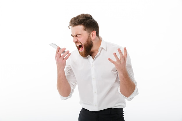 Zły Brodaty Mężczyzna W Ubrania Biznesowe Krzyczy Na Smartphone Darmowe Zdjęcia