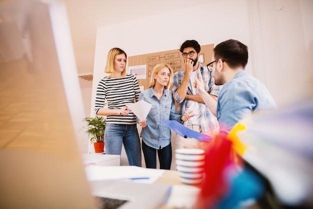 Zmartwiona I Zirytowana Kobieta Rozmawia Z Sfrustrowanym Szefem, Podczas Gdy Współpracownicy Stoją Obok Niej W Biurze Premium Zdjęcia