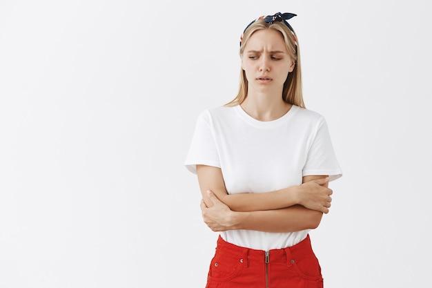 Zmartwiona Młoda Blond Dziewczyna Pozuje Pod Białą ścianą Darmowe Zdjęcia