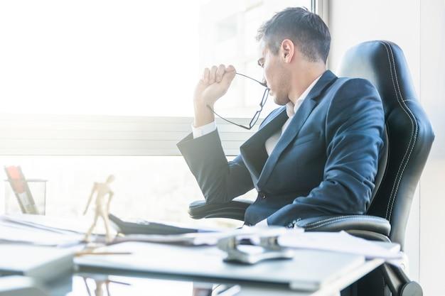 Zmartwiony biznesmena obsiadanie na krześle z zagracającym biurowym biurkiem Darmowe Zdjęcia