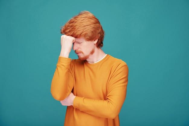 Zmartwiony Młody Rudy Mężczyzna Z Brodą Skupiony Na Umyśle Pocierając Czoło Pięścią Na Niebiesko Premium Zdjęcia