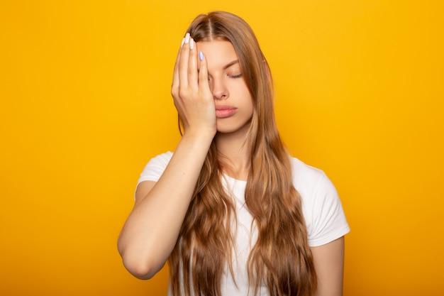 Zmęczona Blondynki Dziewczyna Z Ręką Na Twarzy Odizolowywającej Na Kolorze żółtym Premium Zdjęcia