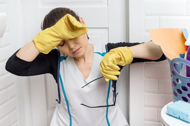 Zmęczona dorosła kobieta czyści łazienki toalety pokój. Premium Zdjęcia