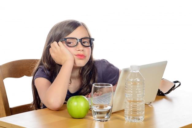 Zmęczona Dziewczynka Z Komputerem I Jabłkiem Premium Zdjęcia